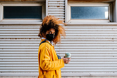 Afro woman with coffee cup standing by wall during COVID-19 - p300m2265327 by Ezequiel Giménez