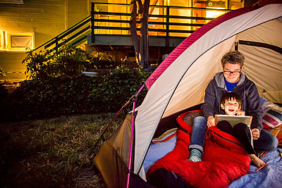 Mother and son using digital tablet in backyard tent - p555m1412115 by Adam Hester