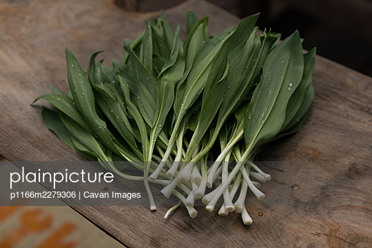 Freshly rinsed wild ramps with water droplets on a wooden background - p1166m2279306 by Cavan Images