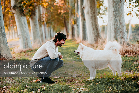 Man talking with dog while crouching at forest - p300m2225566 by Eva Blanco