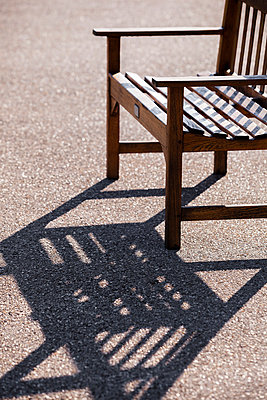 Bench casting a shadow on gravel walk - p1057m1034309 by Stephen Shepherd
