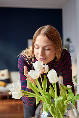 Young woman sniffing at tulips at home - p1124m1589212 by Willing-Holtz