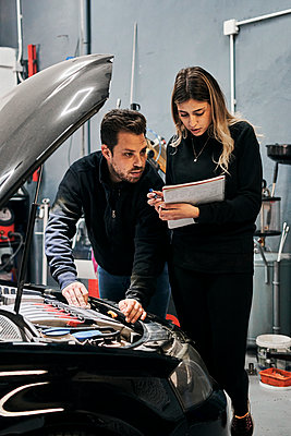Two mechanics help each other in the work of a garage - p1166m2268347 by Cavan Images
