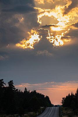 Car passing under dramatic cloudscape - p1418m2002165 by Jan Håkan Dahlström