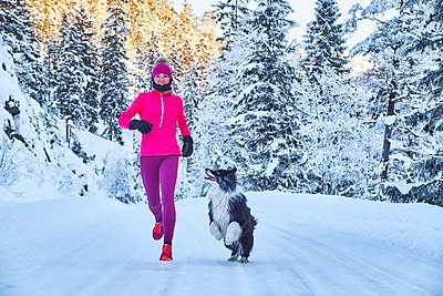 Austria, Tyrol, Karwendel, Riss Valley, woman jogging with dog in winter forest - p300m1356325 by Michael Reusse (alt)