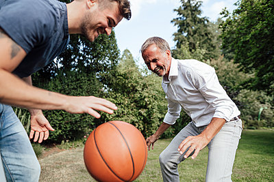 Playful father and son with basketball in backyard - p300m2275099 by Gustafsson