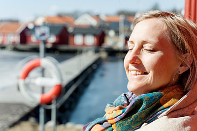 Adult woman standing in harbor with closed eyes smiling - p312m1551867 by Johner Images
