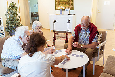 Senior friends playing cards at table in nursing home - p426m2072581 by Kentaroo Tryman