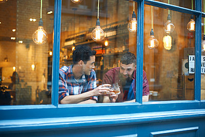 Window view of two men raising a glass in public house - p429m1418087 by Peter Muller