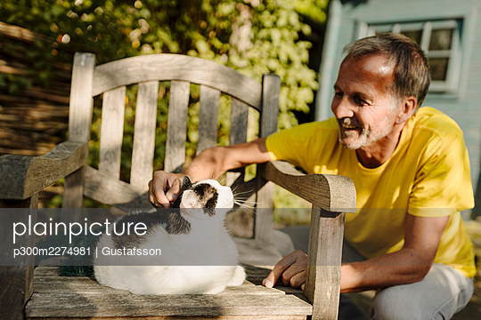 Smiling man crouching while stroking fluffy cat sitting on armchair in back yard - p300m2274981 by Gustafsson