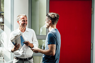 Son discussing with father holding newspaper at home - p300m2275229 by Gustafsson