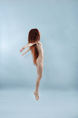 Naked woman with red hair cuts a caper - p427m2244991 by Ralf Mohr