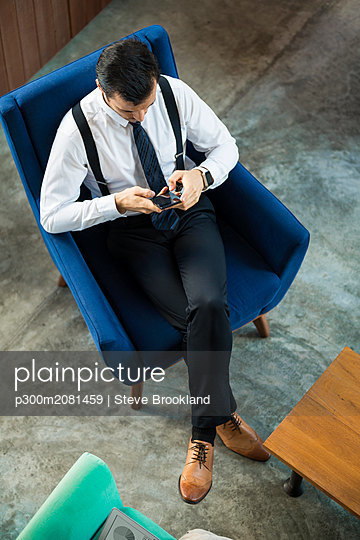 Top view of businessman sitting in blue armchair using smartphone - p300m2081459 by Steve Brookland