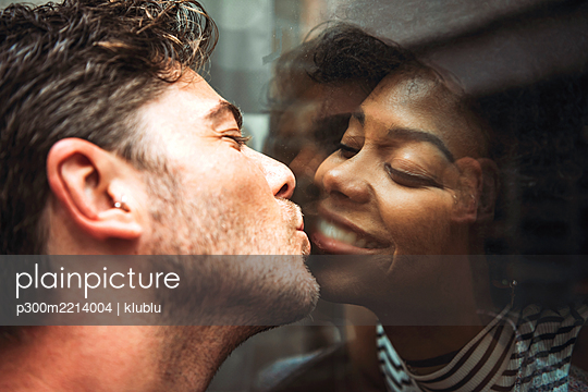 Close-up of romantic man kissing girlfriend through glass window - p300m2214004 by klublu