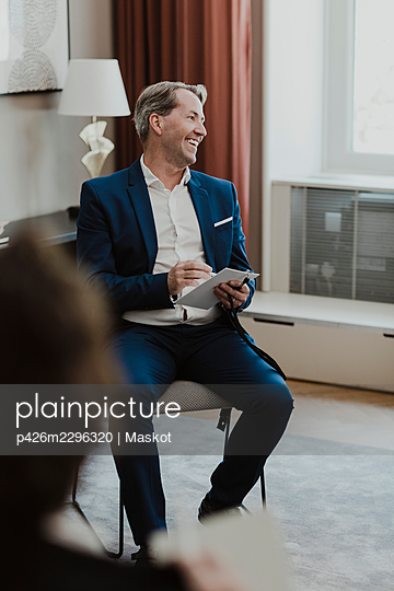 Smiling male entrepreneur with note pad looking away in office - p426m2296320 by Maskot