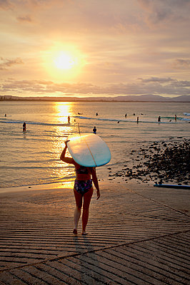 Female surfer carrying board on head walking into sea - p1125m2073235 by jonlove