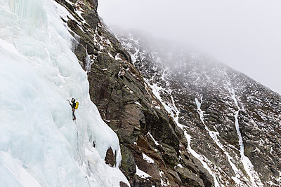 Mid distance view of backpacker ice climbing at White Mountains during winter - p1166m1566940 by Cavan Images