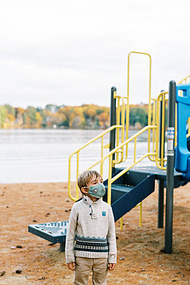 A boy at a playground with his face mask on - p1166m2218370 by Cavan Images