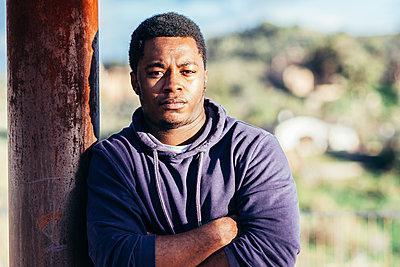 Portrait of an African American boy wearing a purple sweatshirt in an urban space. - p1166m2254948 by Cavan Images