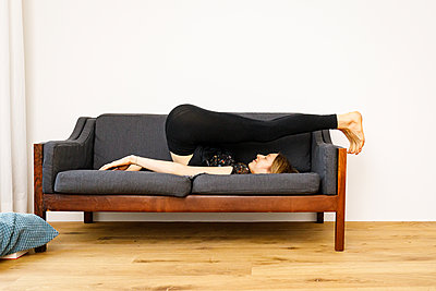 Woman doing gym exercise on the sofa - p294m2151304 by Paolo