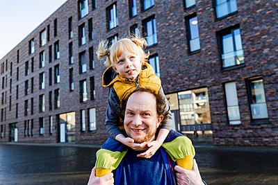Smiling man carrying daughter on shoulder - p300m2277308 by Irina Heß