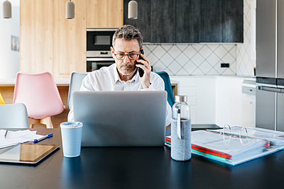 Serious male professional talking on mobile phone while working on laptop at home - p300m2286190 by Josep Rovirosa