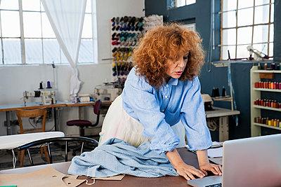 Dressmaker in workshop using laptop - p429m1197935 by Luka Storm