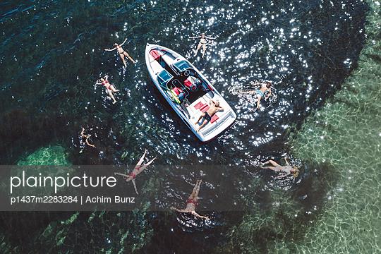 Junge Leute schwimmen neben einem Motorboot - p1437m2283284 von Achim Bunz