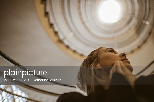 Low angle view of woman standing below spiral staircase - p300m2226791 by Katharina Mikhrin