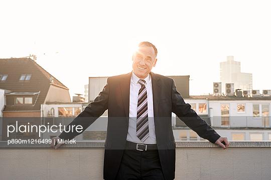 Freundlicher Mann auf dem Balkon - p890m1216499 von Mielek