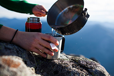 Cropped hands of hiker pouring water in coffee cup - p1166m1211492 by Cavan Images