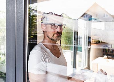 Portrait of pensive man standing behind glass door - p300m1587153 von Uwe Umstätter