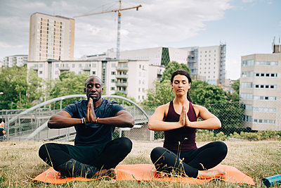 Multi-ethnic friends practicing yoga on field against buildings in city - p426m2036894 by Maskot