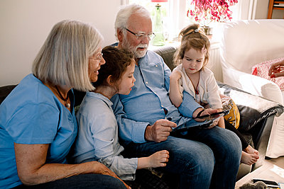 Grandparents and grandchildren using digital tablet while sitting in living room at home - p426m2118401 by Maskot