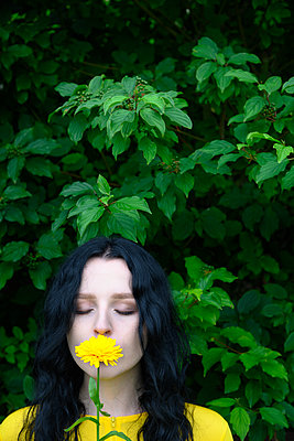 Woman smelling yellow flower - p427m2206375 by Ralf Mohr