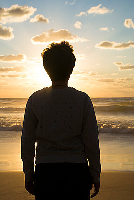 Silhouette of a boy standing on the beach at sunset  - p794m1510977 by Mohamad Itani