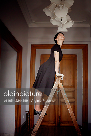 Woman in black dress on a ladder - p1105m2244899 by Virginie Plauchut