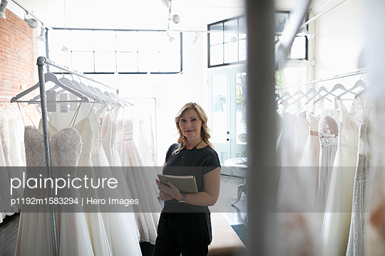 Portrait confident bridal boutique owner checking wedding dress inventory - p1192m1583294 by Hero Images