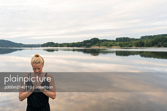 Young woman with folded hands at a lake - p300m2140110 by Joseffson