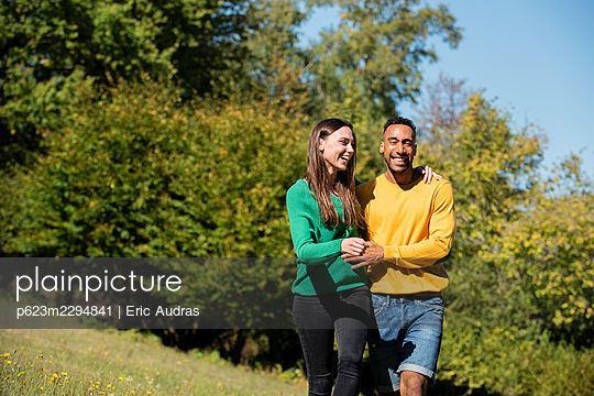 Smiling young couple walking in public park - p623m2294841 by Eric Audras