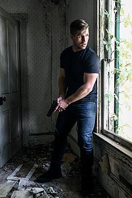 Bewaffneter Mann in seinem Versteck - p1019m1424625 von Stephen Carroll