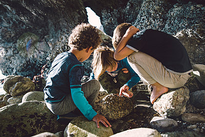 Friends playing with rocks while crouching at beach - p1166m1554244 by Cavan Images