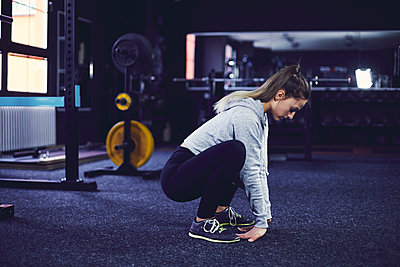 Side profile of young woman stretching on the floor at fitness centre - p1166m2095521 by Cavan Images