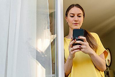Mid adult woman using smart phone while leaning on window - p300m2276079 by Oxana Guryanova