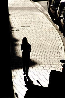 Silhouette einer Frau die im Abendlicht einen Gehweg entlanggeht - p9792184 von Jaeckel
