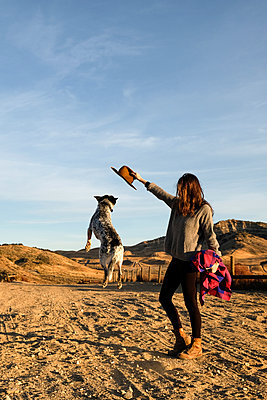 Full length of young woman playing with dog at desert against sky - p1166m1577715 by Cavan Images