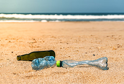 Glass and plastic bottles lying on beach sand - p300m2202592 by klublu