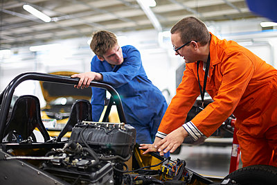 College mechanic students discussing racing car engine in repair garage - p429m1227306 by Peter Muller
