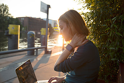 Young woman using laptop outside cafe, Berlin, Germany - p429m2077831 by Tamboly