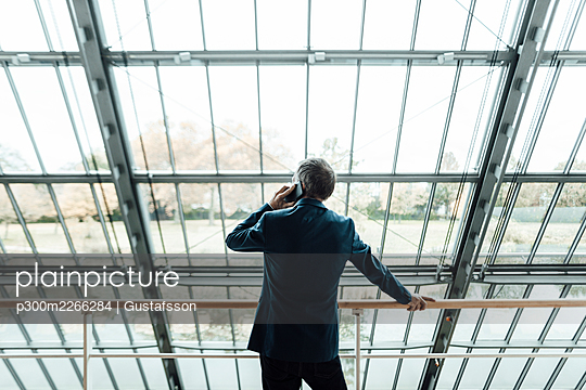 Businessman talking on mobile phone while standing at railing in corridor - p300m2266284 by Gustafsson
